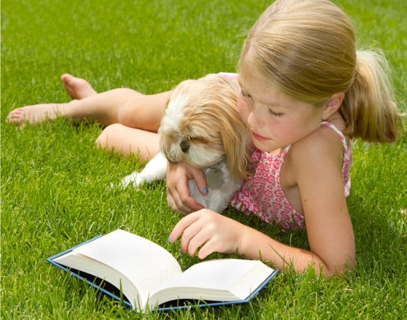 Girl reading to a dog in the grass